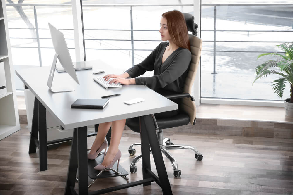 A woman is using a footrest while working