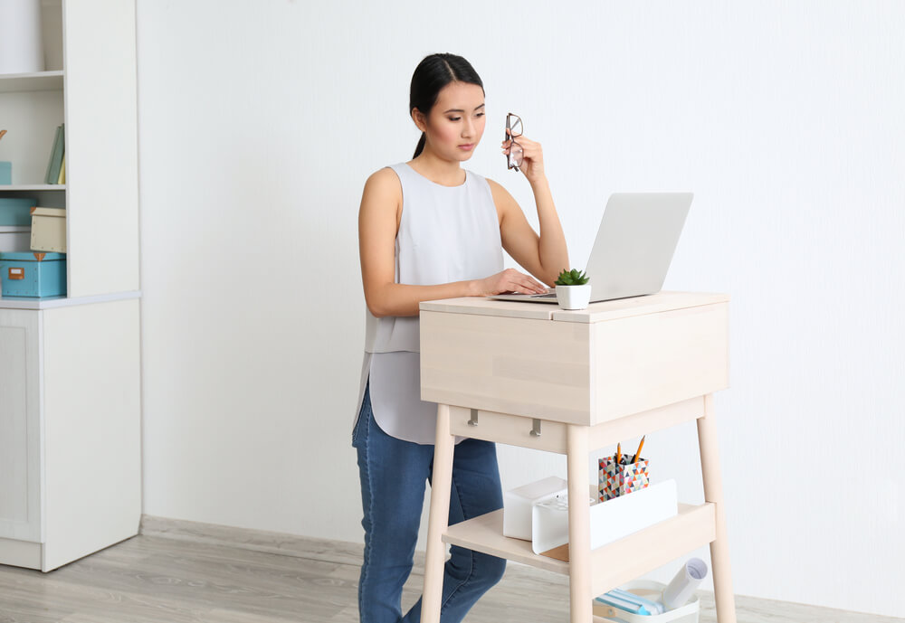 Asian woman typing on laptop at DIY stand-up desk