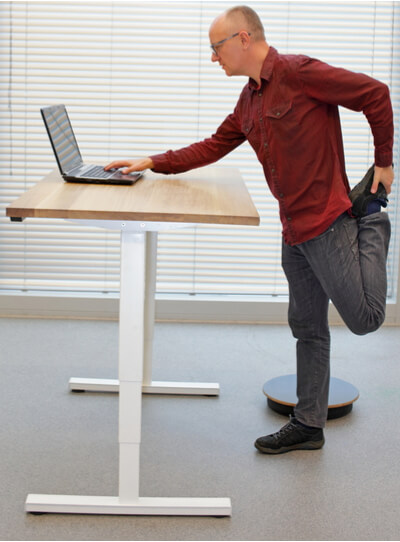 Man is standing in improper posture during standing office work