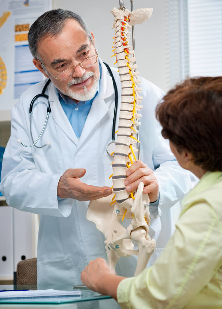 Physiotherapist shows the problem areas on the model of the spine to senior patient
