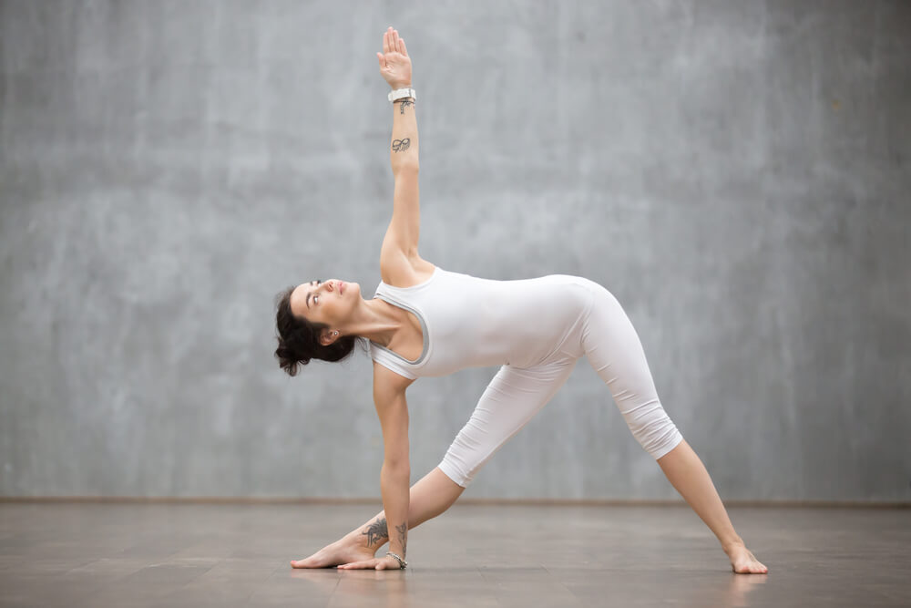 Woman is staing in Standing in Utthita Trikonasana yoga pose