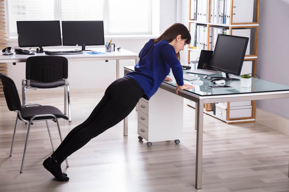 Young Businesswoman Doing Push Up On Office sit-stand Desk
