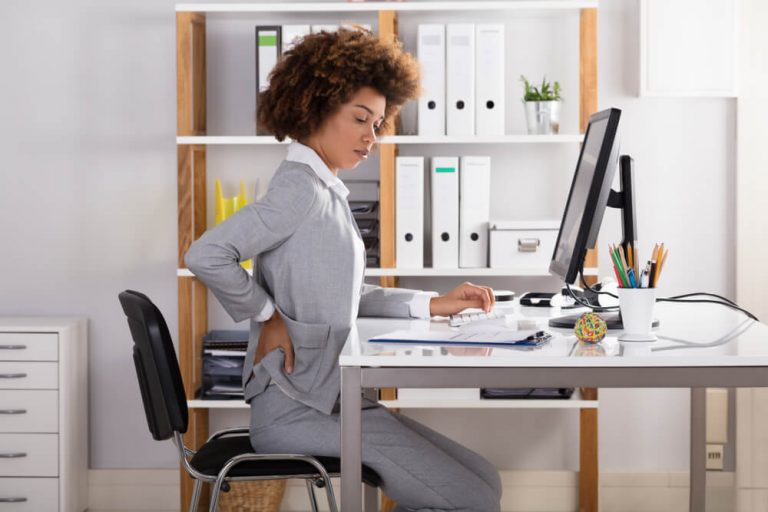 Young Businesswoman Suffering From Back Pain at work