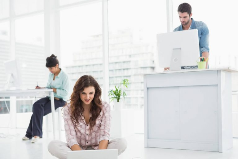 businesswoman sitting on the floor using laptop with colleagues standing behind