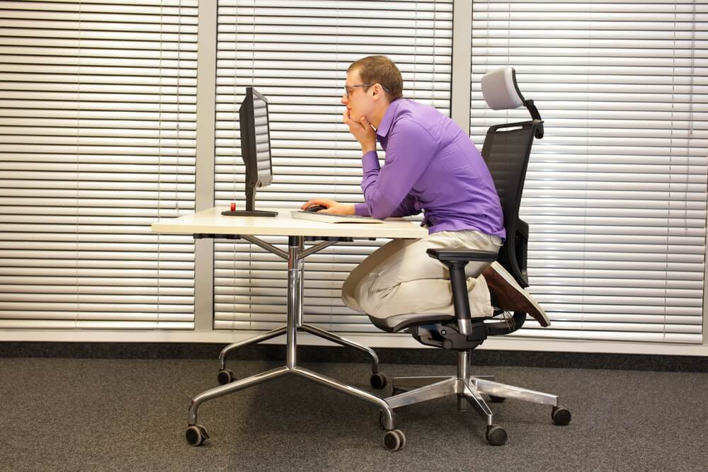 Office employee is sitting in slouching position on ergonomic chair