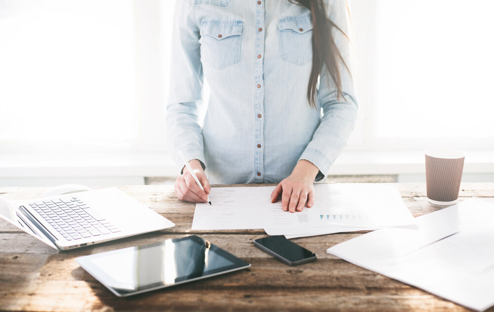 Woman is working at a wooden standing desk