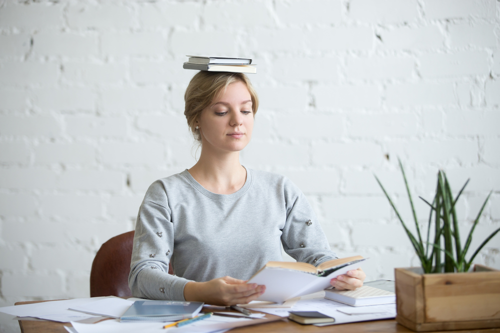 woman is sitting straight at the desk with books on her head