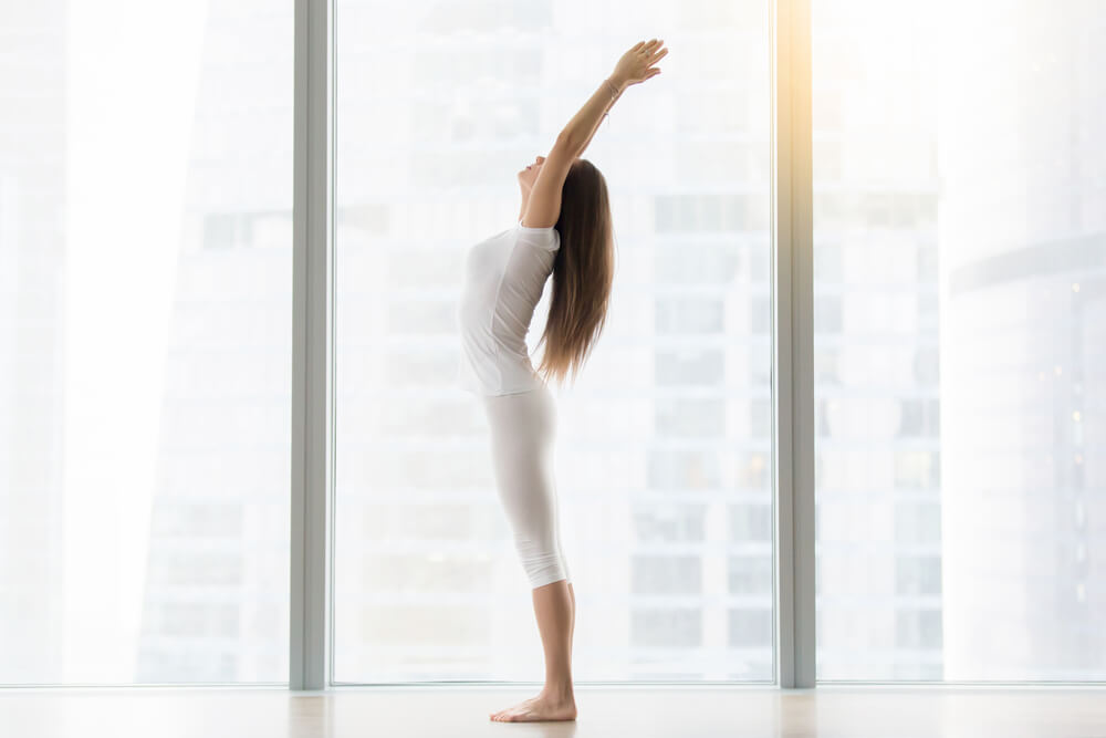 Young woman is standing in Tadasana - Mountain Pose
