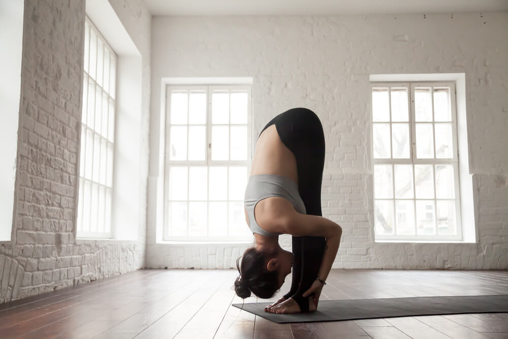 Woman standing in uttanasana - standing forward fold pose