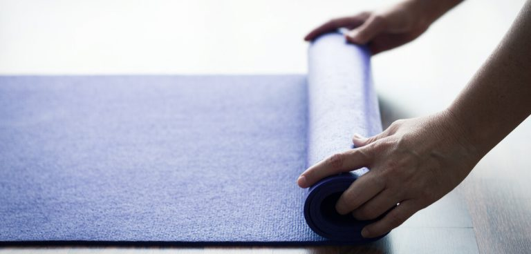 Hands of woman unrolling purple standing anti-fatigue mat