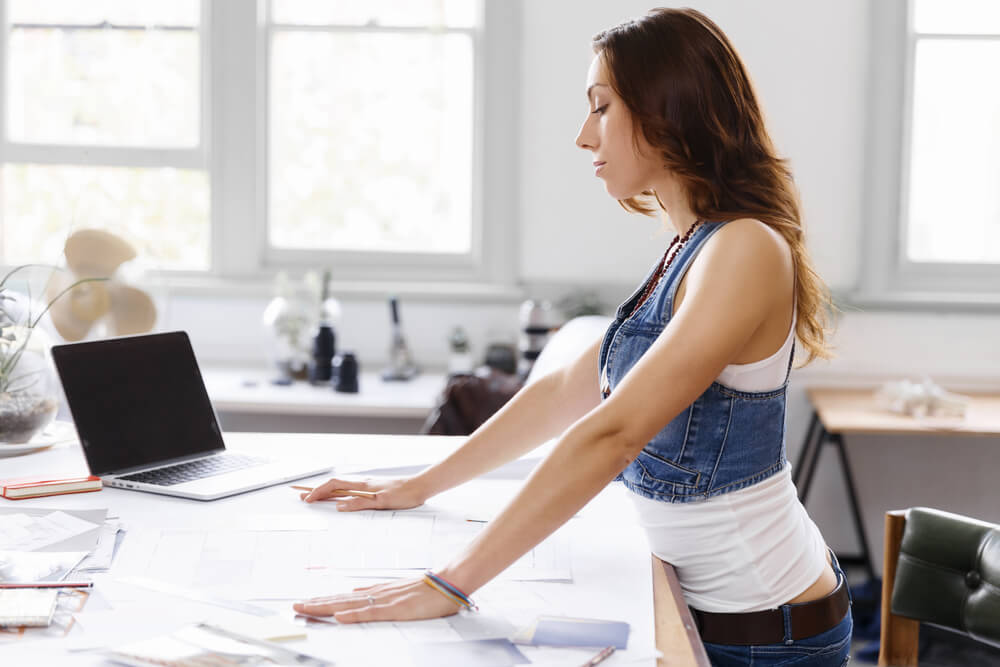 Young woman is standing at sit-stand desk in creative office