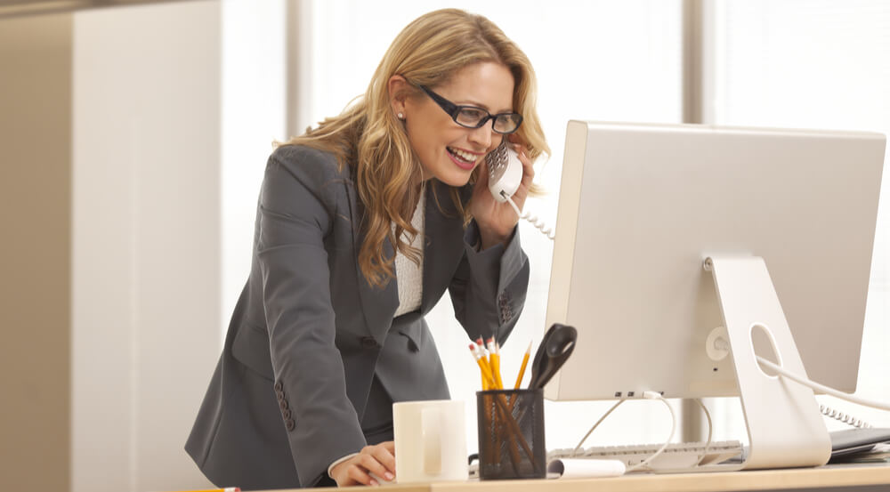 businesswoman is talking over the phone while looking at her computer