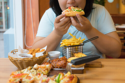 obese asian woman eating junk food