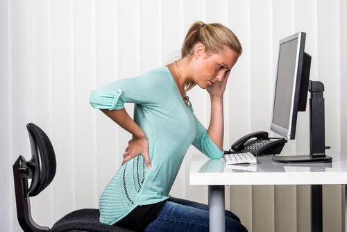 woman sitting with pain in her back