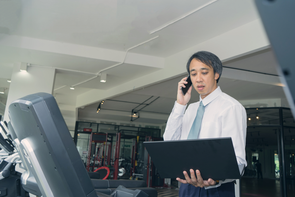 Businessman busy use smart phone and laptop on treadmill machine