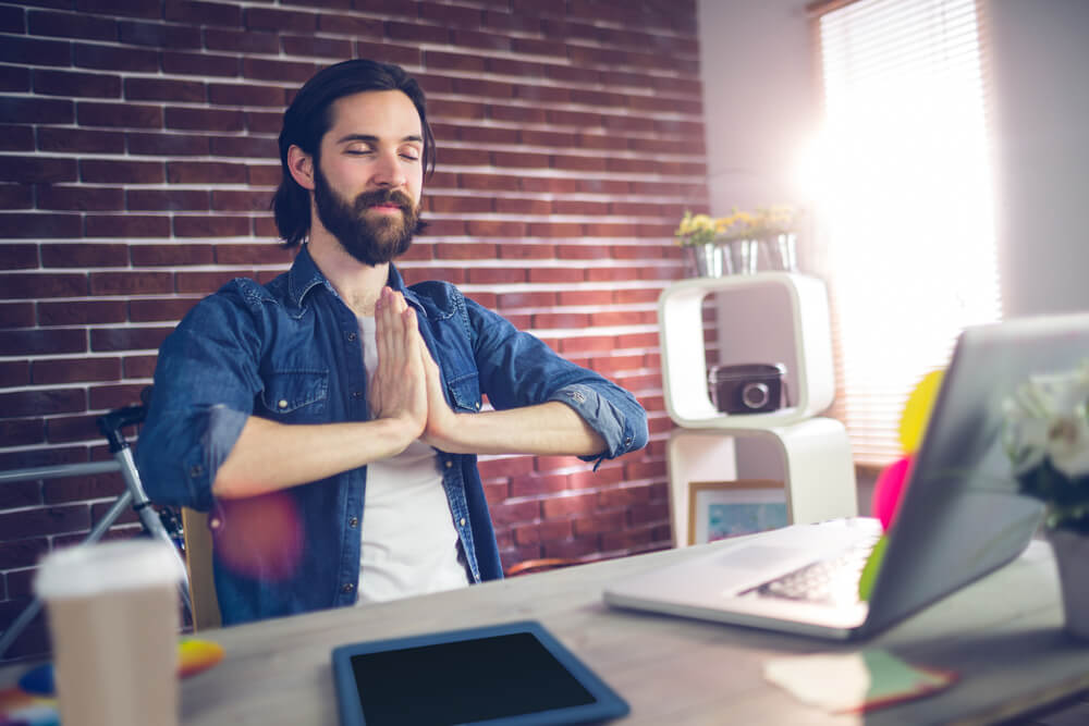 Businessman with hand clasped doing standing yoga poses in creative office