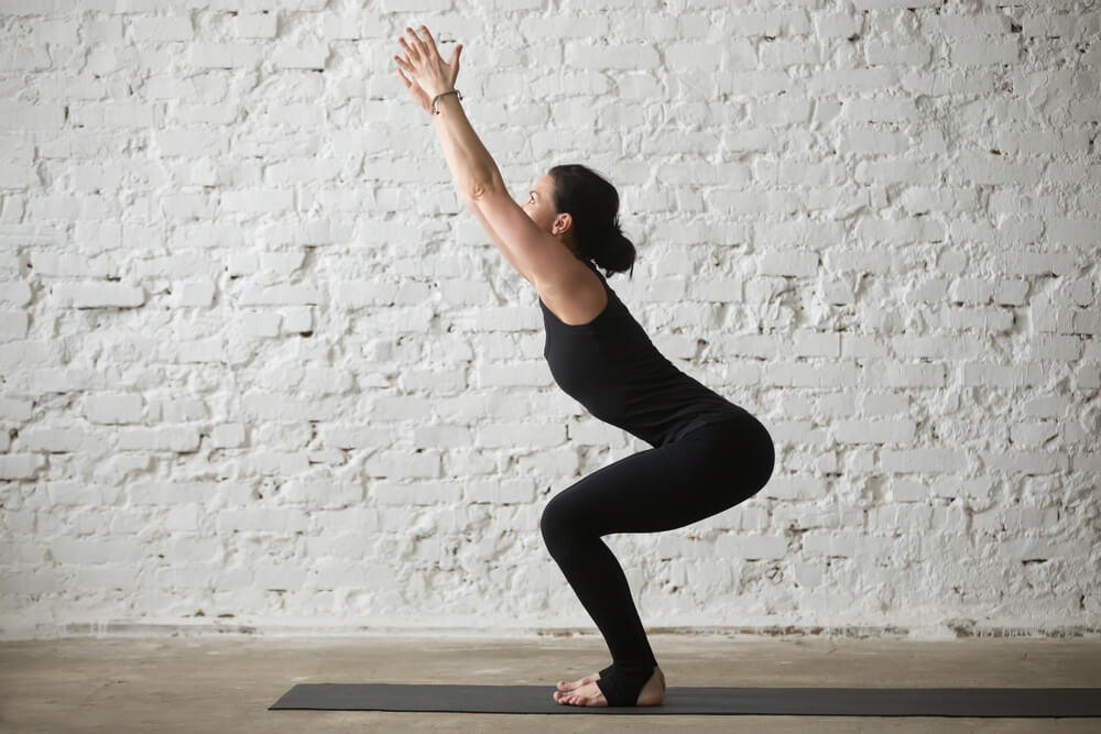 Woman is standing in Utkatasana - chair pose