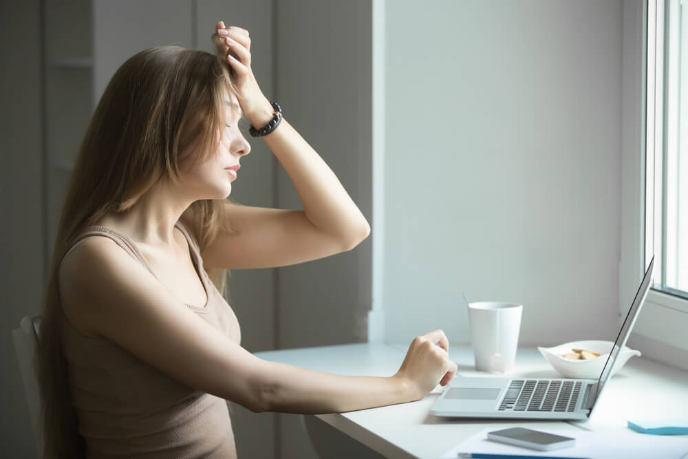 Young woman tired of sitting at laptop