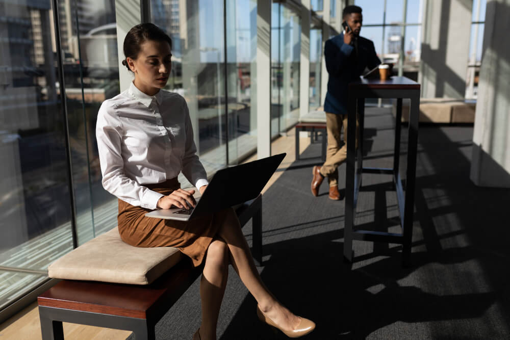 Office Employee is sitting on bench in modern office