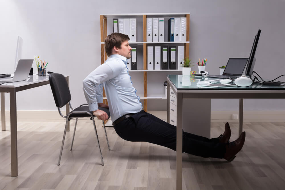 Young Businessman Doing Triceps Dips In Office