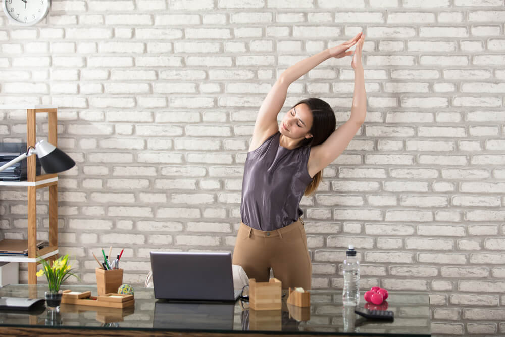 Young Businesswoman Stretching At Workplace In her modern Office