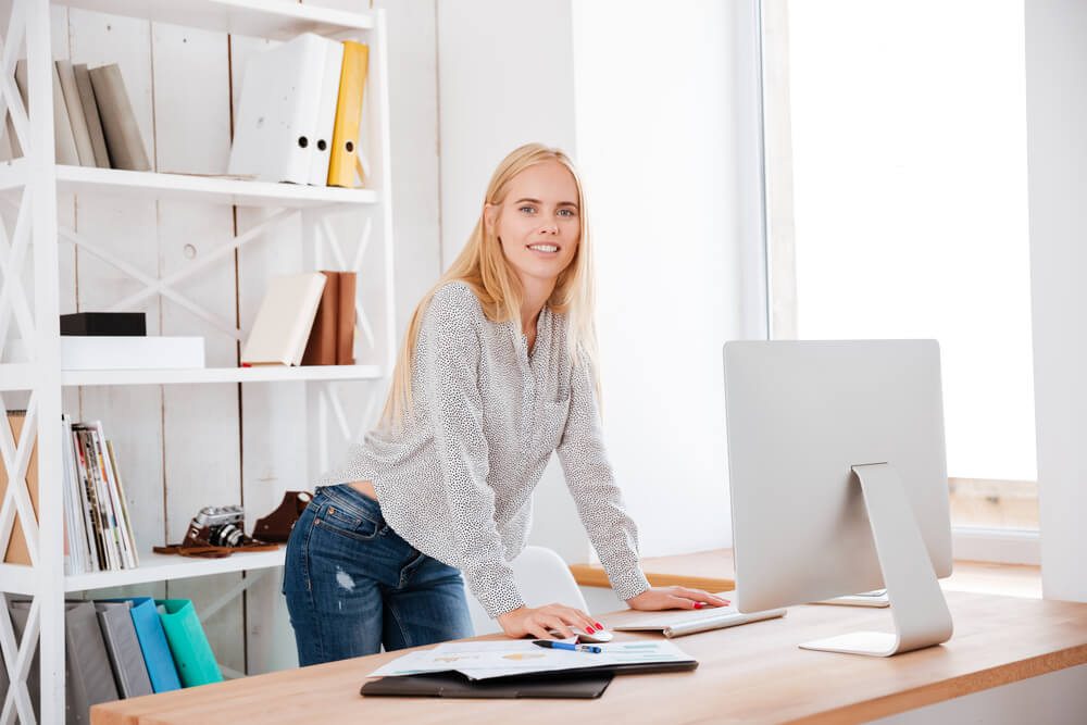 attractive business woman standing and working at her adjustable desk