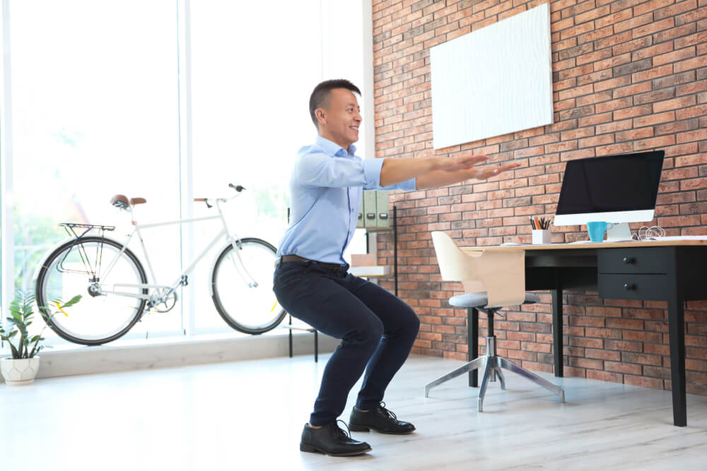 Asian businessman doing exercises at his standing desk