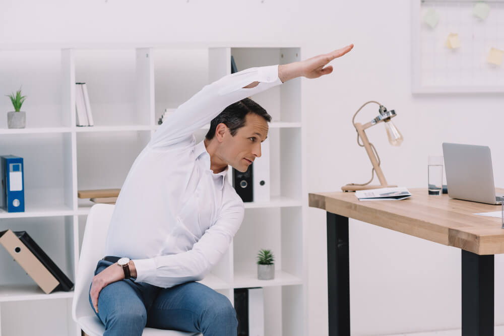 businessman doing side bend on his ergonomic chair