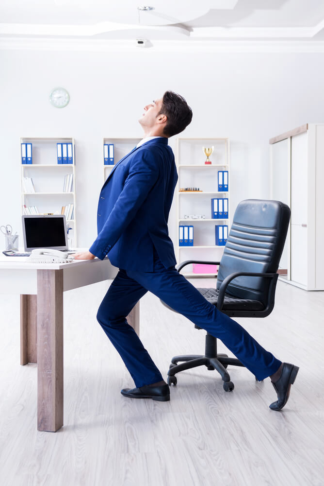 businessman doing lateral leg raise at workplace