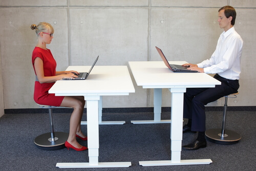 men and women working in correct sitting posture at sit-stand desks