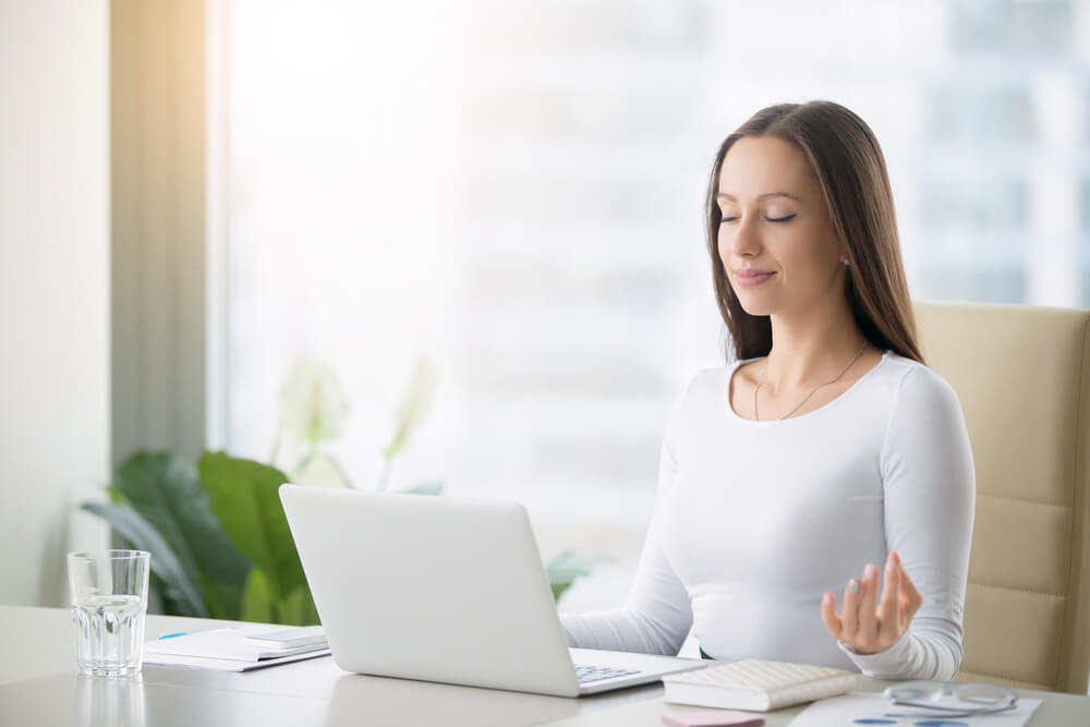 Woman is practicing meditation at the office desk