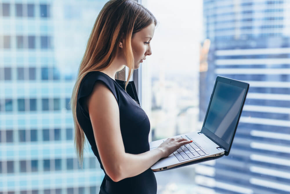woman is holding laptop while standing at work