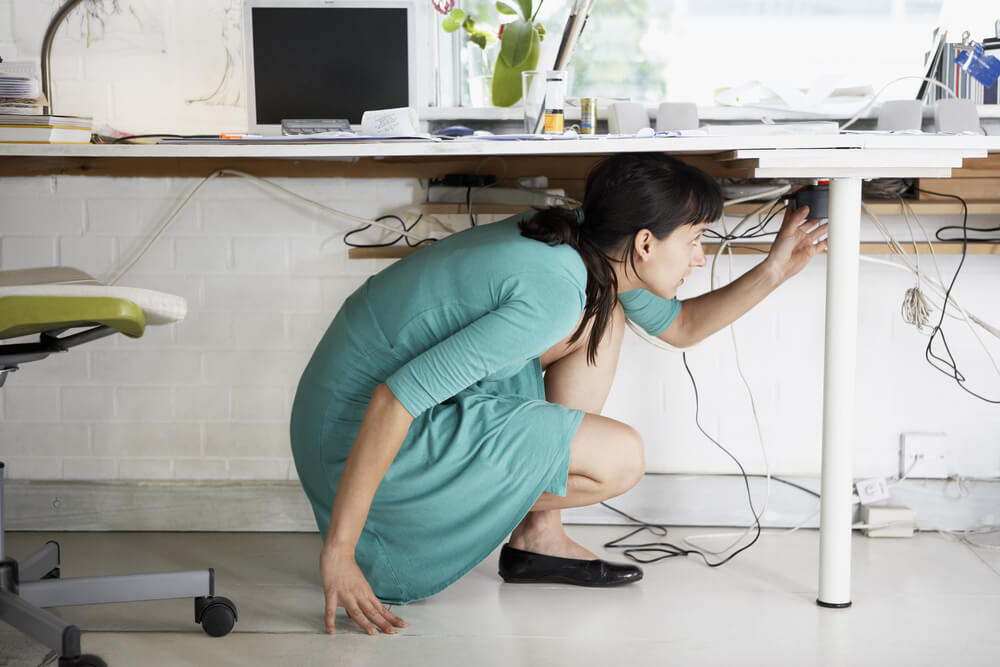 young businesswoman adjusting cables under desk