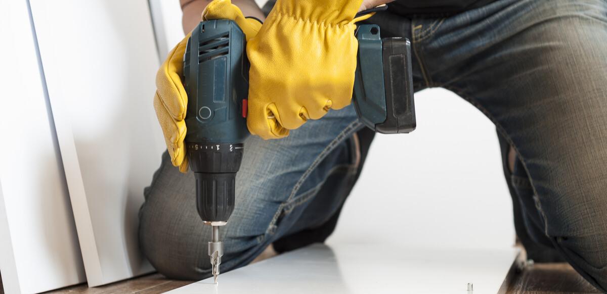 man drills a hole when assembling diy standing height desk