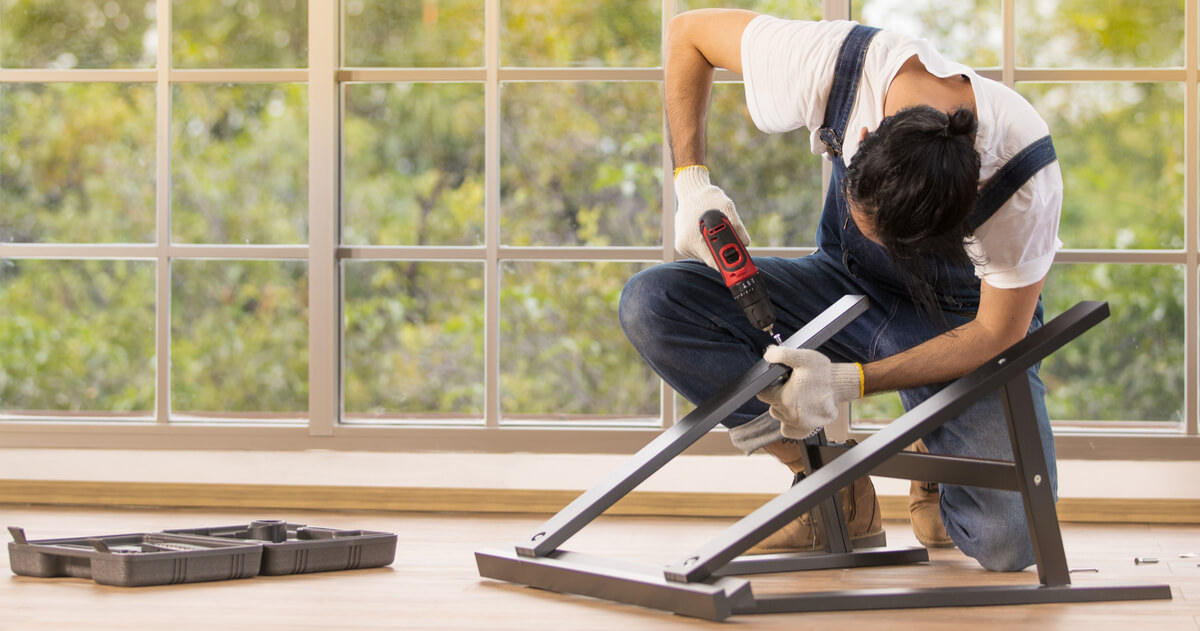 Young man working as handyman, assembling wood table