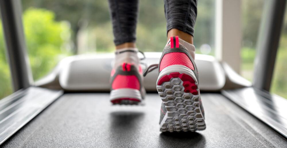 woman is walking on a treadmill desk workstation
